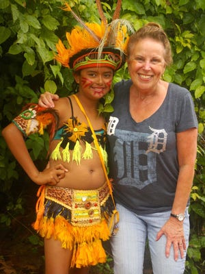 Carol Lyons of Macomb Township sports the Old English D as she poses with an indigenous girl from the village of Boca da Valeria along the Amazon River in Brazil, which she visited with her husband in March.