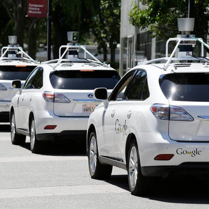 A row of Google self-driving cars outside the Computer