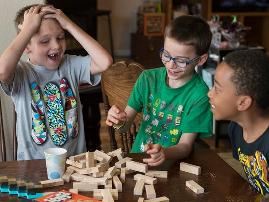 Olly Ajluni, 7, center, plays with his cousins Troy