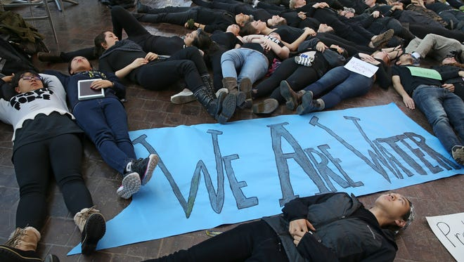 """University of Rochester student Yuxin Leo Liu, Class of 2019, born in China now living in Albany, bottom, joins with nearly 70 others during the """"Human Oil Spill"""" held at the University of Rochester Tuesday, Nov. 15, 2016. The protest was in support of those protesting the Dakota Access Pipeline in North Dakota."""