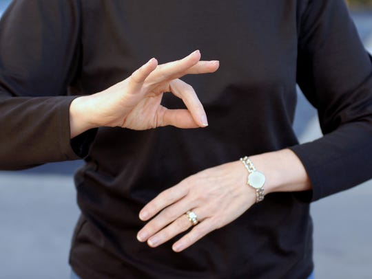"Sign language for ""French""; or ""okay"" hand signal."