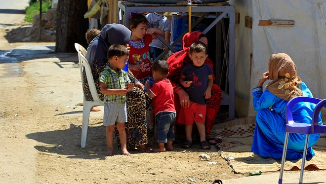 Syrian refugees sit with their children outside their tents at a Syrian refugee camp in Lebanon in July.