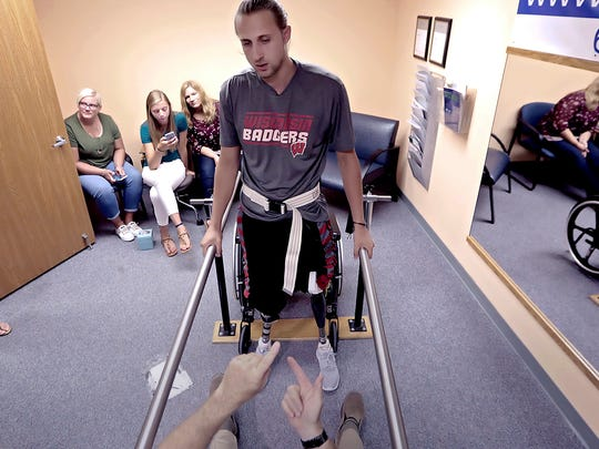 In an Aug. 10, 2017 photo, Collin VanderGalien walks for the first time in two months while trying out a new set of prosthetic legs during an appointment at Sisson Mobility Restoration Center, Inc. in Monona, Wis. VanderGalien lost both of his legs in an explosion at the Didion Milling Plant in Cambria, Wis. in May.