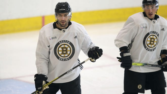 Boston Bruins center Patrice Bergeron, left, and left wing Brad Marchand at camp on Tuesday in Boston.