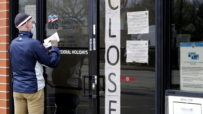 A man writes information in front of Illinois Department of Employment Security in Chicago, on April 30. IDES was experiencing severe staffing shortages before COVID-19 hit, creating problems when thousands more people each week began applying for unemployment benefits.