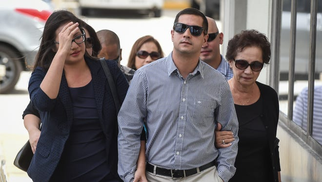 Jared Ada, general manager of Guam Medical Transport, third from right, enters the District Court of Guam to enter a plea on Jan. 5. Ada and another GMT employee are accused of illegally billing Medicare and TriCare for millions of dollars for ambulance services that did not warrant insurance coverage.