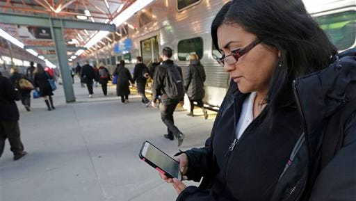 In this Friday, March 13, 2015 photo, Marilu Rodriguez checks a news website on her smartphone before boarding a train home at the end of her work week in Chicago. Young adults have a reputation for being connected to one another, yet disconnected from the news, but a new survey has found, that mobile devices and, in some cases, social networking are keeping them more engaged with the broader world around them than previously thought. Rodriguez' smartphone is her most frequent portal to the world, as she surfs social networking and news sites, often on her train ride to and from her work as a coordinator for a nonprofit organization. (AP Photo/M. Spencer Green)