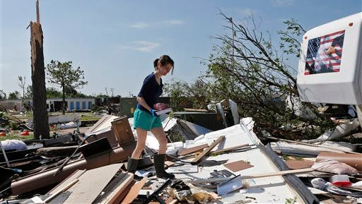 In this Thursday, May 7, 2015 photo, Dillan Taylor salvages items from her destroyed recreational vehicle in Oklahoma City. Communities that were threatened by a pack of more than 50 tornadoes earlier this week shift their attention from cleaning up to getting ready for the next storm. The menacing clouds had barely vanished before forecasters warned of another system that could bring twisters through the weekend. (AP Photo/Sue Ogrocki)