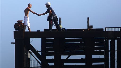 A member of the Fort Lauderdale Fire Rescue Tactical Rescue Team rescues a naked man on top of a raised drawbridge on Friday, May 22, 2015 in Fort Lauderdale, Fla.   Witnesses said the unidentified man was swimming in the river earlier and was walking across the railroad bridge Friday morning when it began to rise, forcing him to scamper to the top.