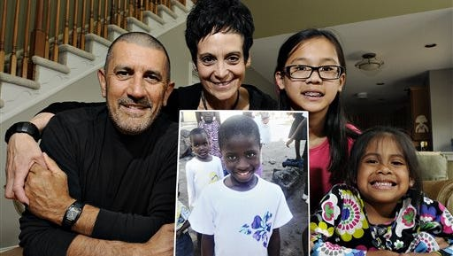 In this photo taken on May 9, 2014, Michael Fichera  and Linda Scotto with their two daughters Emma, 11, and 6-year-old Kearly pose with a photograph of their adopted Congolese daughter Miriam at their home in Doylestown, Pa. The adoption process by the couple , was virtually completed by the fall of 2013 and they were getting ready to travel to Congo when a suspension was imposed. Miriam, has continued to live in an orphanage; she'll turn 9 in August. After nearly two years of frustration, several hundred American families now have reason to hope that children they are adopting from Congo may finally be allowed to travel to the United States. (Rick Kintzel/The Intelligencer via AP)