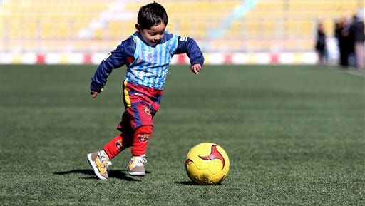 Murtaza Ahmadi, a five-year-old Afghan Lionel Messi fan plays football, at the Afghan Football Federation Stadium in Kabul, Afghanistan, Tuesday, Feb. 2, 2016. The Afghan Football Federation plans to set up a meeting between  Messi and Ahmadi who became an Internet sensation when photos circulated of him wearing an improvised Messi shirt made from a plastic bag.