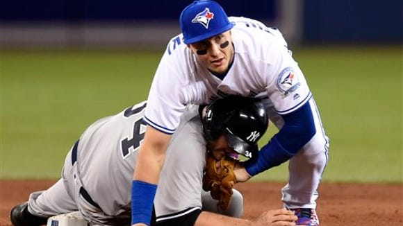 Toronto Blue Jays' Troy Tulowitzki looks to first after forcing out New York Yankees' Brian McCann during the fourth inning of a baseball game Thursday, April 14, 2016, in Toronto. Carlos Beltran was safe at first, and Alex Rodriguez scored.