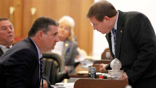 Rep. Nelson Dollar, right, talks to Rep. David Lewis during a special session of the North Carolina General Assembly at the Legislative Building in Raleigh, N.C. on Friday. North Carolina Republicans stripped the incoming Democratic governor of some of his authority on Friday and they were on the cusp of an even greater power grab, an extraordinary move that critics said flies in the face of voters.