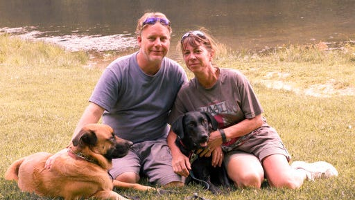 In this Aug. 22, 2015 photo provided by Amy Hunter, John and Amy Hunter are pictured with their dogs, Apollo, left, and Rubi, a black Labrador retriever, in Brown County State Park south of their home in Indianapolis, Ind. The couple is childless by choice and Amy is a stay-at-home pet mom.
