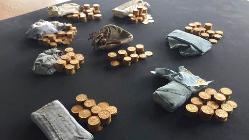 """The 913 gold coins which were found in a piano, are displayed at Ludlow Museum  in Ludlow, England  Thursday April 20, 2017, where they are being kept under lock and key. As a mystery surrounds the identity of the rightful heirs to a treasure trove of gold coins. British officials say they have been unable to trace the rightful heirs to a trove of gold coins  worth a """"life-changing"""" amount of money. The school that owns the piano and the tuner who found the gold are now in line for a windfall after a coroner investigating the find declared it treasure."""
