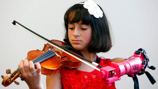 "Ten-year-old Isabella Nicola Cabrera plays her violin with her new prosthetic at the engineering department of George Mason University in Fairfax, Va., Thursday, April 20, 2017. Isabella never had any doubt it would come together. ""I felt right away that I'd be able to play,"" she said. ""I've always had perseverance."""