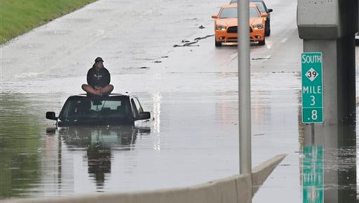A stranded motorist sits on top his car as he awaits rescue from the flooded Southfield Freeway, Monday  in Dearborn, Mich. The Michigan State Police issued an advisory Monday evening, urging drivers to avoid non-essential use of all metro Detroit freeways after heavy rain and thunderstorms left roads flooded and impassable. Interstate 75 at I-94 in Detroit has been shut down in both directions, according to the Michigan Department of Transportation.