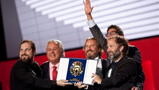 Spanish film director, Carlos Vermut,  left, celebrates with his film staff after receiving the Golden Shell for his film, '' Magical Girl'' at the 62nd San Sebastian Film Festival in San Sebastian, northern Spain, Saturday.