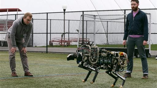 In this Oct. 24, 2014 photo, researchers Randall Briggs, left, and Will Bosworth monitor a robotic cheetah during a test run on an athletic field at the Massachusetts Institute of Technology in Cambridge, Mass. MIT scientists said the robot, modeled after the fastest land animal, may have real-world applications, including for prosthetic legs. (AP Photo/Charles Krupa)