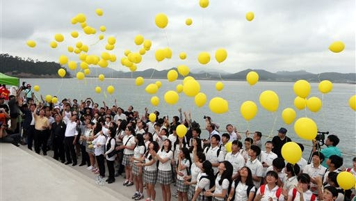 Relatives of missing passengers of the sunken ferry Sewol and citizens release yellow balloons in memory of the deceased and return of still missing passengers aboard the ship 100 days after the ferry sunk,  at a port in Jindo, South Korea, Thursday, July 24, 2014. South Korean police said Tuesday that a badly decomposed body found surrounded by liquor bottles in a field last month was that of a fugitive billionaire businessman blamed for April's ferry disaster that killed more than 300 people. (AP Photo/Hyung Min-woo, Yonhap) KOREA OUT