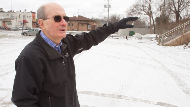 Brighton Downtown Development Authority board chair Bob Herbst talks about the plans to build a multi-story parking structure where he stands, on the lot at the corner of West and North streets in downtown Brighton.
