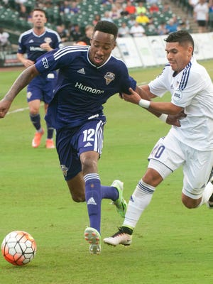 Louisville City FC midfielder Mark Anthony Kaye tries to free himself from Orlando City B midfielder Johnny Mendoza as Mendoza tries to pull Kaye away from the ball during LouCity's 2-1 loss on Saturday, July 30, 2016.