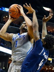 University of Memphis forward Dedric Lawson (left) is fouled by Jackson State University defender Derek Roscoe (right) while putting up a shot during first-half action at FedExForum.