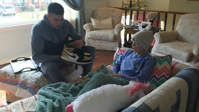"""Michael Porter Jr. gives Elizabeth Joy """"Lizzy"""" Wampler a pair of size 14 shoes while visiting her at her home."""