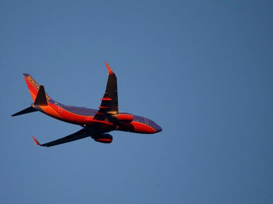A Southwest Airlines plane flies in late evening light