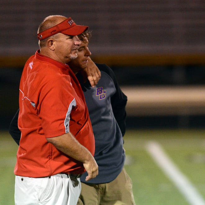 Logan Elm head coach Scott Bartholomew embraces his son, Bloom-Carroll coach Wade Bartholomew, after Friday night's game in Carroll. Father and son faced off as head coaches for the first, and last, time.
