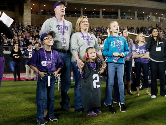 Jenny Faber of Ankeny, center -- -- her daughter Abby wearing the No. 2 Trevone Boykin TCU jersey -- and the rest of the Faber family stand in the end zone during a presentation where they were introduced to the stadium in the first half of a game against West Virginia Thursday in Fort Worth, Texas.