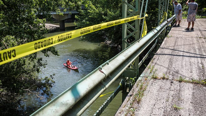 County workers put up caution tape and temporary signs to discourage swimmers from jumping from a former bridge over the White River on county road 750-west Monday morning.