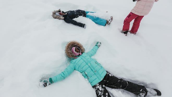 (foreground clockwise) Makenzye Massey and her sisters Jordyn Massey and Madisyn Massey, all of Flint, make snow angels while sledding at Flint Southwestern Academy in Flint after a snowstorm blanketed the area on Friday February 9, 2018.