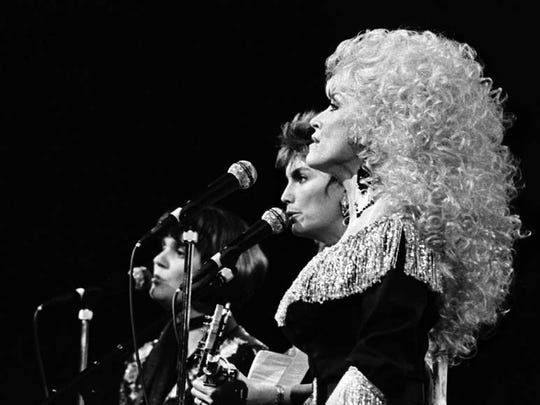 Linda Ronstadt, left, Emmylou Harris and Dolly Parton perform in 1986 during the CMA Awards show at the Grand Ole Opry House. In September a three-disc collection of unreleased Trio songs — a band featuring the three — will be made available.