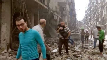 In this Thursday, April 28, 2016 image made from video and posted online from Validated UGC, a man carries a child after airstrikes hit Aleppo, Syria.