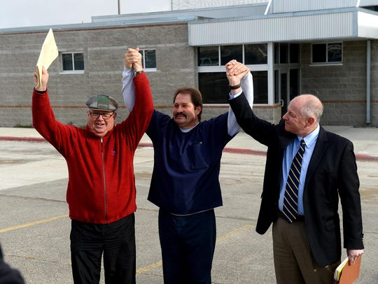 Barry Beach, center, flanked by Jim McCloskey of Centurion Ministries, left, and attorney Peter Camiel, raise their arms in victory Nov. 20, 2015, as Beach is released from Montana State Prison in Deer Lodge.