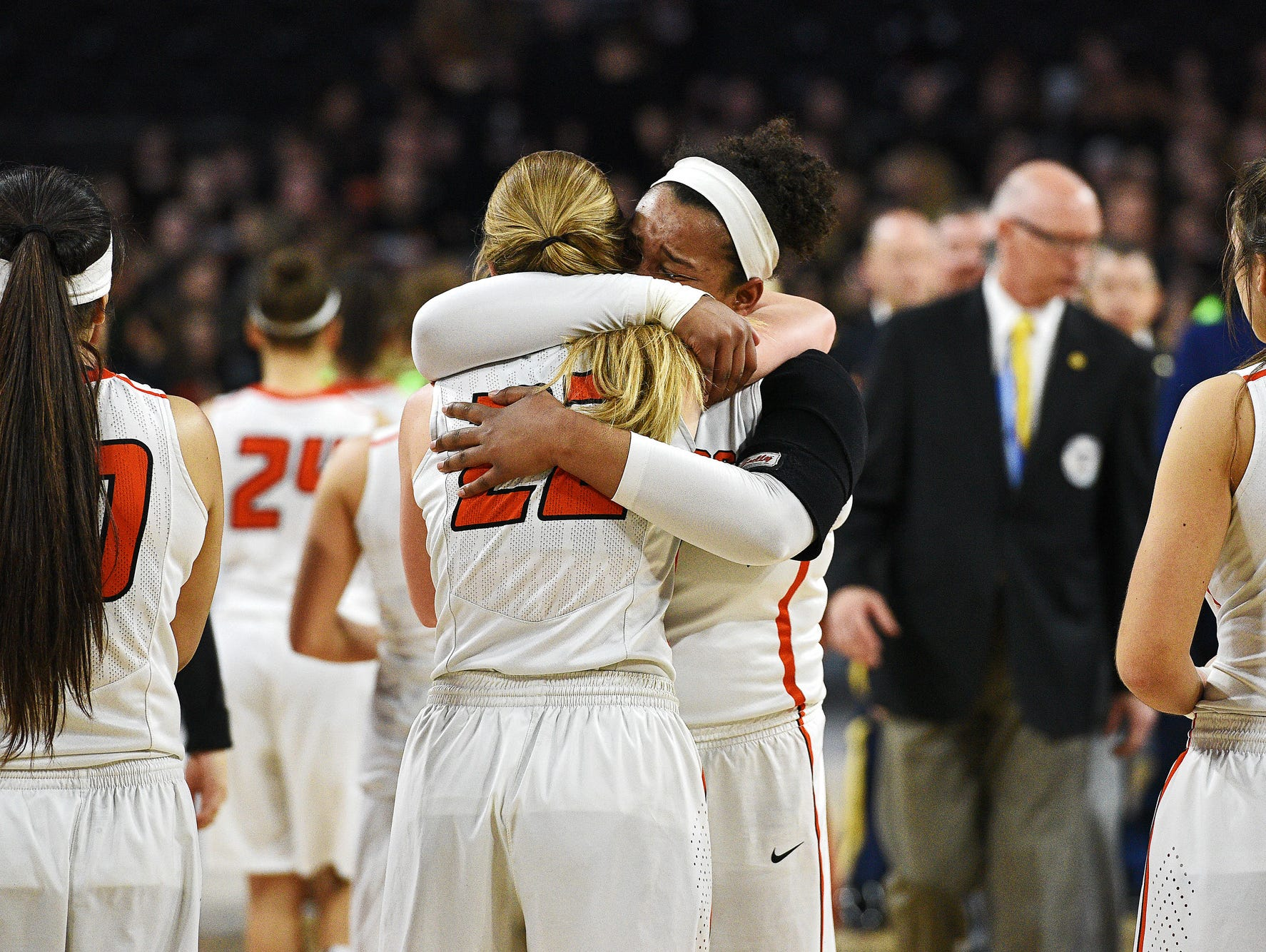 Washington's Anna Goodhope (22) and Sydney Arrington (54) hug after their 75 to 64 loss to Aberdeen Central in the South Dakota Class AA State Girls Basketball Tournament championship game Saturday, March 19, 2016, at the Denny Sanford Premier Center in Sioux Falls.