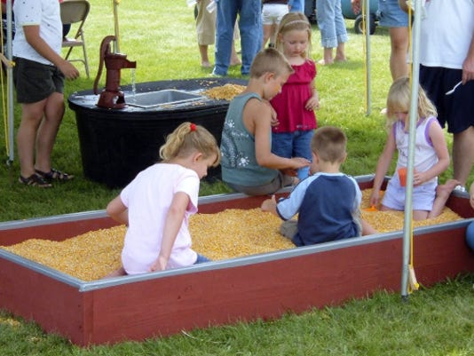 Children enjoy playing in a cornbox at last year's Rural Life Festival on the grounds of Newburg United Methodist Church.