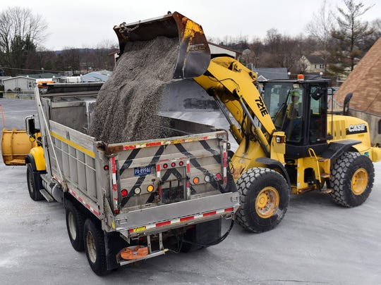 Scott Schuchman loads a salt mix into a plow truck