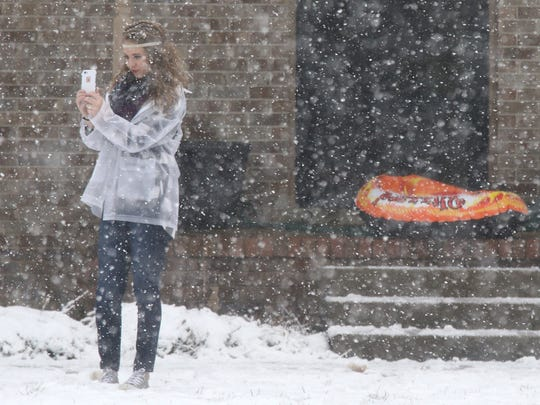 Snow continues to fall as Chloe Frankes, 13, takes photos in the wintry weather as she waits for her friends to come outside to join her on Friday, Jan. 22, 2016, in Murfreesboro.