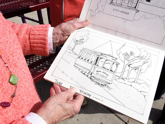 Joyce M. Wittenhagen shows a coloring book made by the Benton County Historical Society in 1988 on Thursday, June 2, at Lake George.