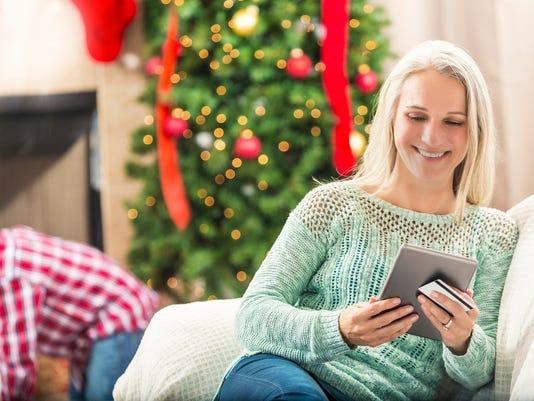 Beautiful senior woman shops online at Christmastime