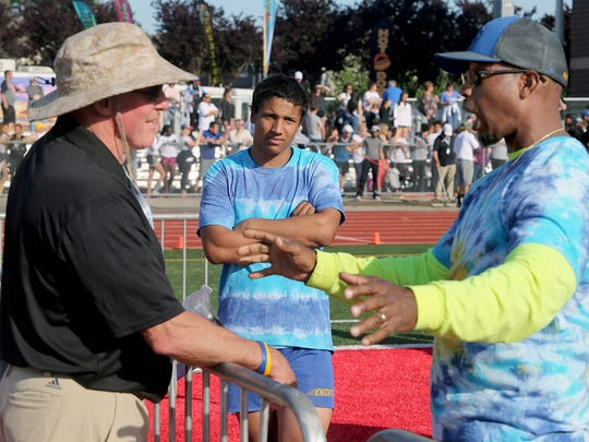 Bremerton pole vaulter Jesse Smith (center) listens while Knights track and field coach Daniel McInnis (right) talks to official Steve Slaven during Thursday's state track and field championships at Mount Tahoma High School.