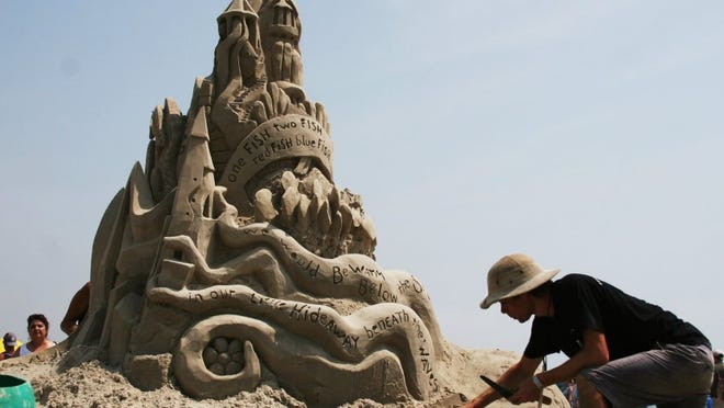 Emerson Schreiner of Michigan works with his aunt on a sculpture called 'Gifts from the Sea' in April 2016 during the Texas Sandfest in Port Aransas.