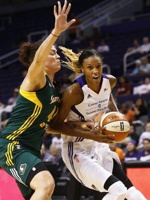 Phoenix Mercury forward DeWanna Bonner drives to the basket with pressure from Seattle Storm forward Kristen Mann during WNBA preseason action on Thursday, May 28, 2015, at US Airways Center in Phoenix, AZ.