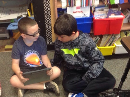 Two Stoy students share an iPad.