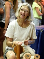Peggy Schott uses a spinning wheel during the Fleece to Shawl show at the Lebanon Area Fair, Tuesday, July 26.