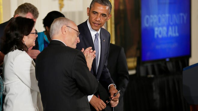 Rabbi David Saperstein, left, claps as President Obama approaches to sign an executive order to protect LGBT employees from federal workplace discrimination at the White House on July 21, 2014.