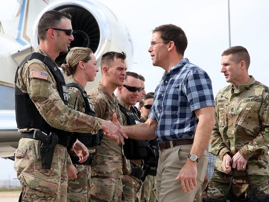Secretary of the Army Mark T. Esper, in checkered shirt, greets a military police detachment before boarding a plane to Washington, D.C. following an all-day visit to Fort Bliss on Thursday.
