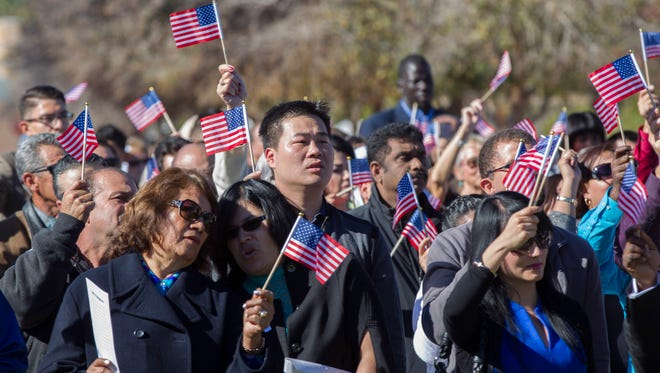 More than 200 new citizens wave American flags at the end of the Chandler Citizenship Naturalization Ceremony at the Chandler Public Library in Chandler, AZ on January 17, 2015.